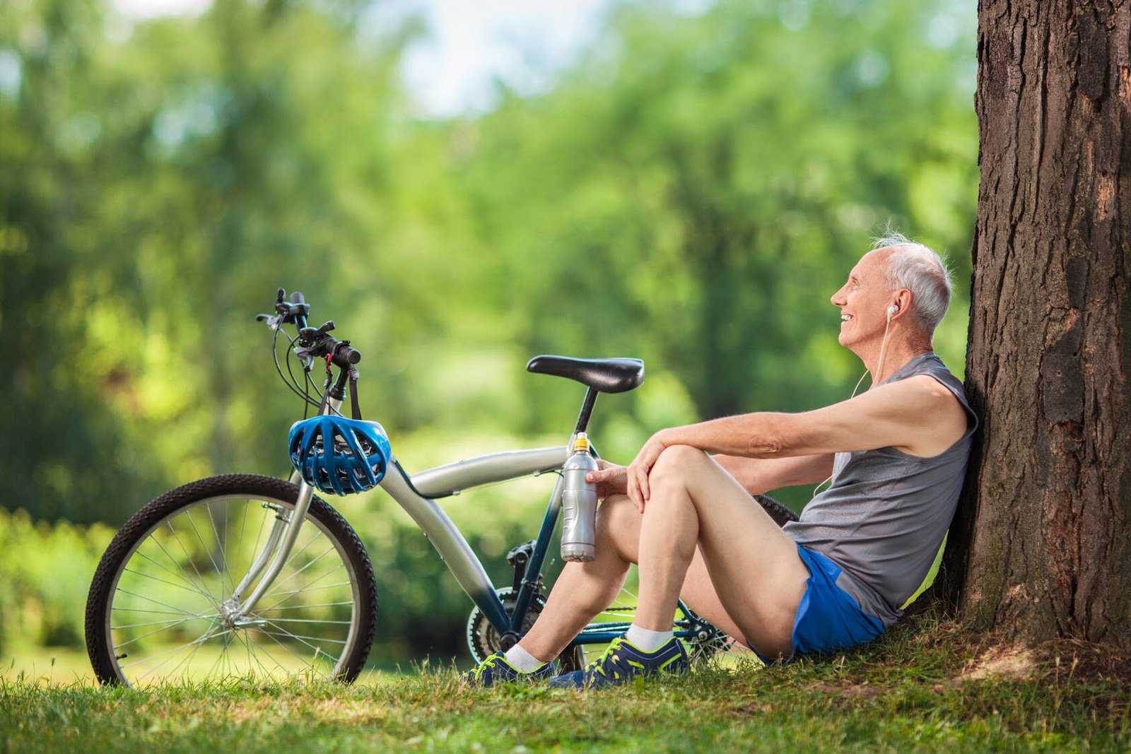 an-elderly-biker-sitting-under-the-tree-while-listening-to-a-music
