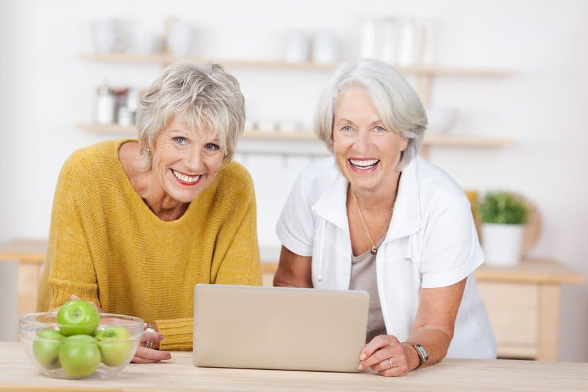 two-happy-senior-women-with-a-laptop-in-the-kitchen
