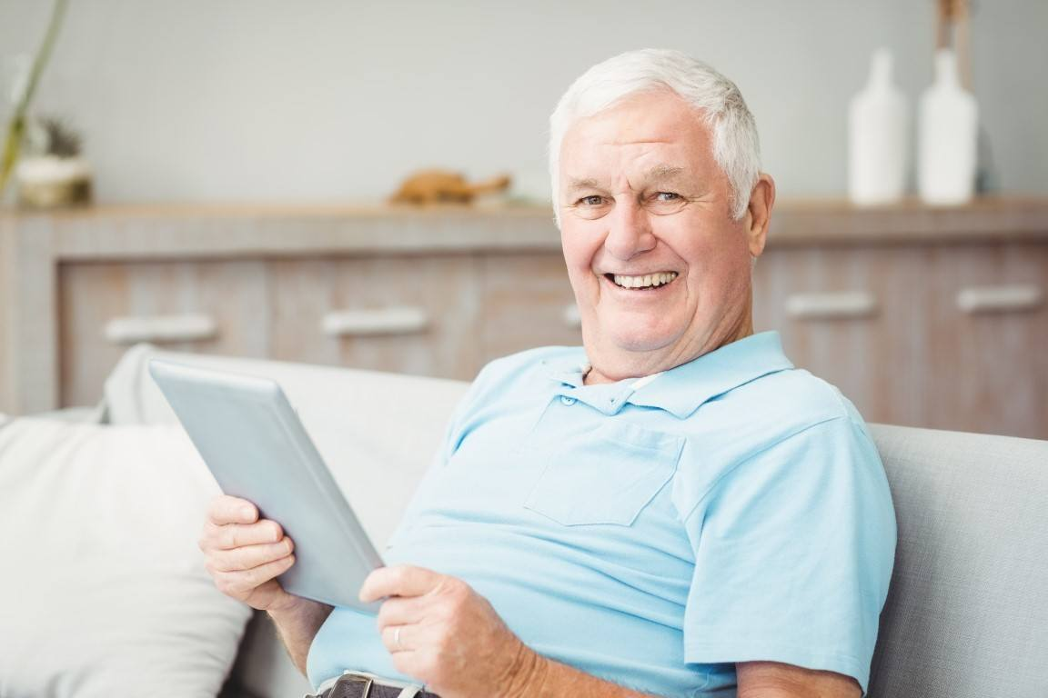 senior man in his living room using a tablet