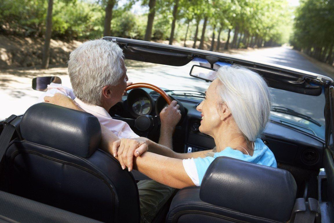 happy senior couple riding in a sports car