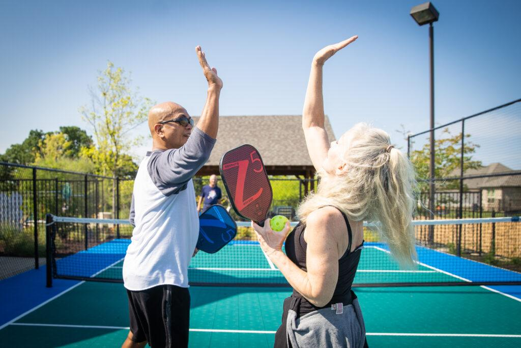 man and women high fiving on tennis court