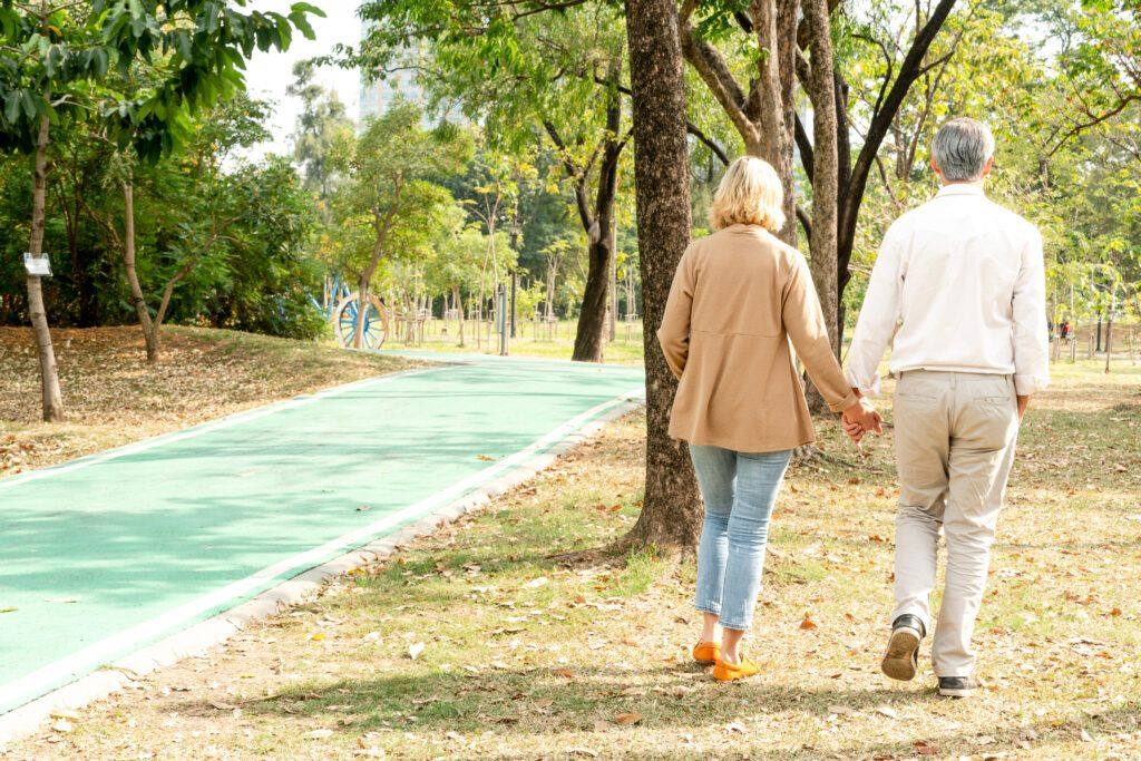 man and woman holding hand and walking at park bqmyhdh 2