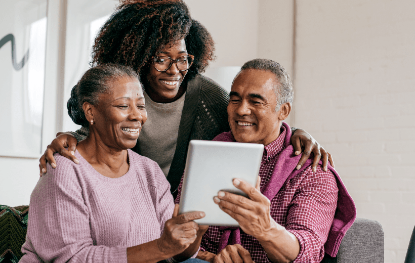 older couple looking at ipad with daughter